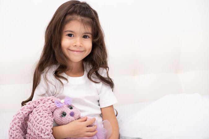 穿着家装的小女孩和泰迪兔坐在家里的床上