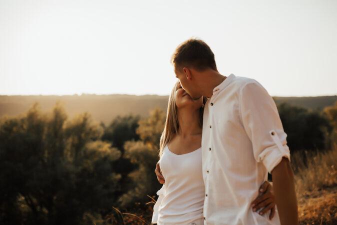 这是一幅浪漫迷人的白衣可爱情侣的肖像画 他们面对面地拥抱在一起 看着美丽的风景