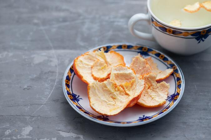 把桔皮放在盘子里和热水杯里