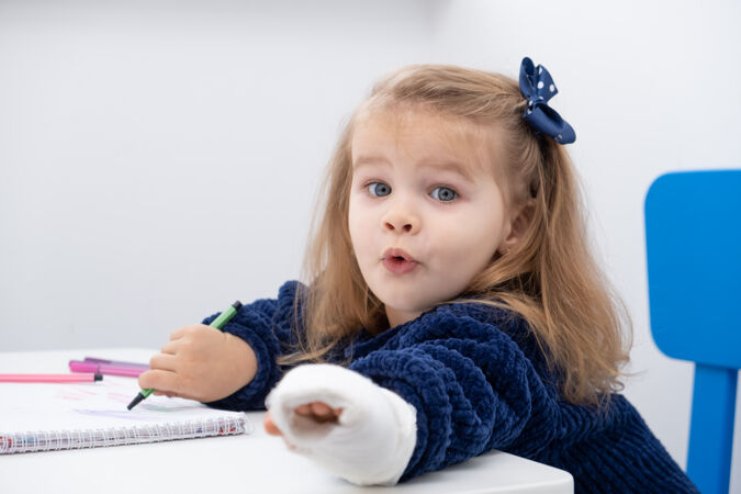 坐在桌边用马克笔试着画画的小女孩手拿石膏