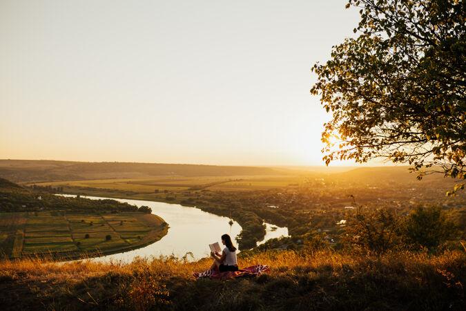 年轻的女游客坐在山上 以河流为背景 日落时在山上看书