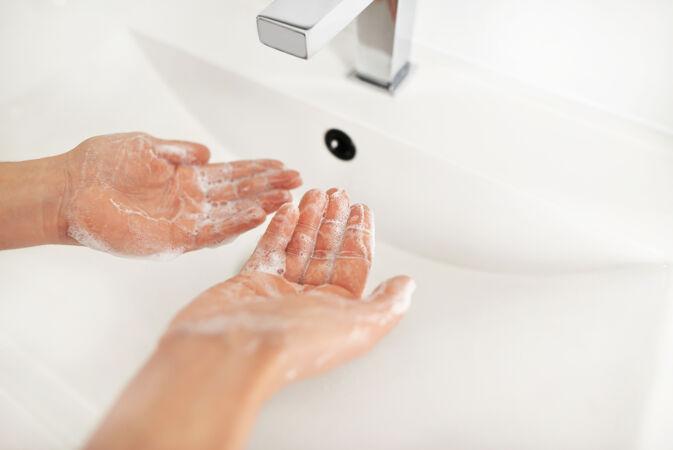 在水龙头下用肥皂洗手