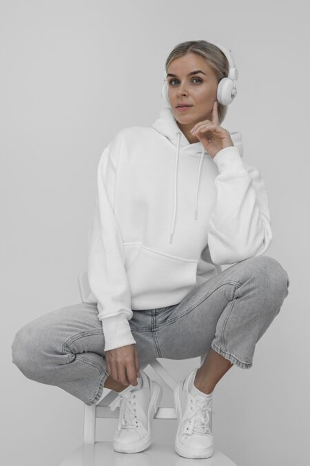 戴着耳机的时尚女士连帽衫的前视图