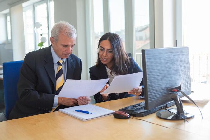 女性专业人士在工作场所向客户解释文件细节严肃的业务领导咨询财务或法律专家团队合作或合作理念