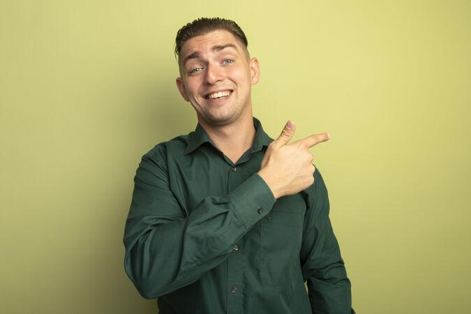 一个穿着绿衬衫的年轻帅哥 脸上带着微笑 食指指向一边