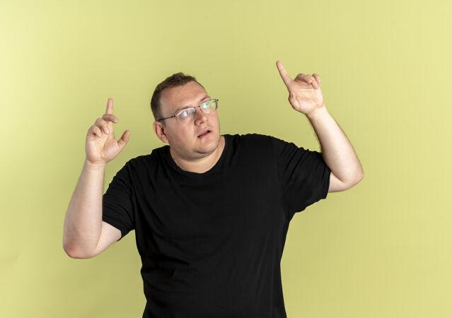 一个戴着眼镜 身穿黑色t恤的超重男子抬头困惑地指着 食指站在浅色的墙上