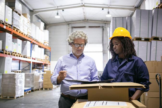 认真成熟的检查员在检查仓库和填写表格时咨询黑人女员工复印空间 前视图劳动和检查概念