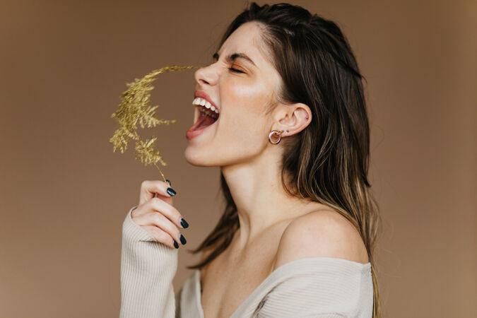 兴奋的戴着耳环的女孩摆出了一副鲜花的姿势在拍摄过程中 一位深肤色的年轻女士笑了起来