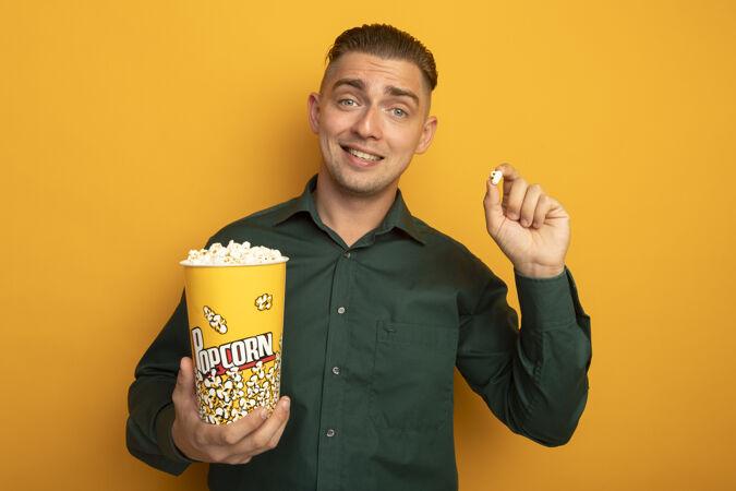穿着绿衬衫的年轻帅哥捧着装满爆米花的水桶开心而积极地笑着