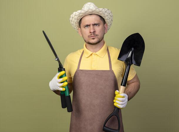 年轻的园丁 穿着连体衣 戴着帽子 戴着工作手套 拿着铲子和树篱剪 表情严肃