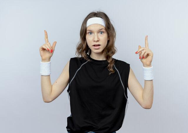 穿着黑色运动服的年轻健身女孩 戴着头带 手指朝上 站在白色的墙上