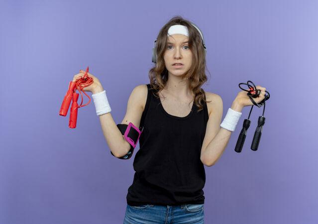 穿着黑色运动服的年轻健身女孩 头上带着两条跳绳 困惑地站在蓝色的墙上