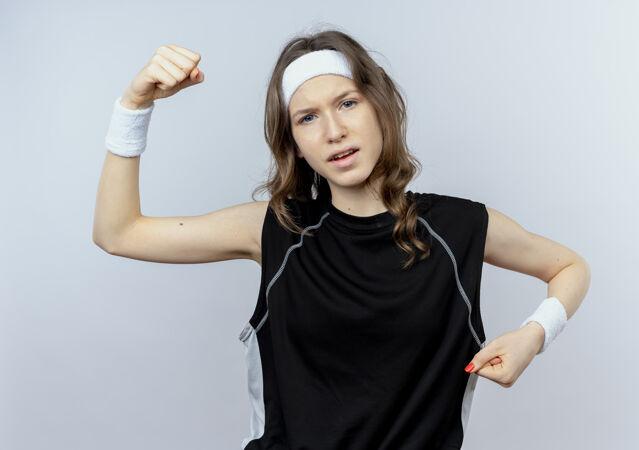 身穿黑色运动服 头箍高举拳头的年轻健身女孩站在白色的墙壁上 看上去很自信
