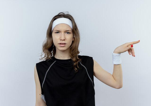 穿着黑色运动服的年轻健身女孩 表情混乱 手指指着站在白墙上的一边