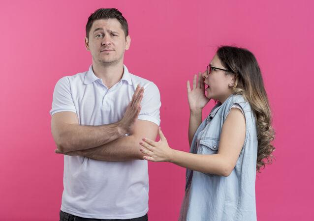 一对穿着休闲服的年轻男女不高兴地对她的男朋友大喊大叫 而他站在粉红色的墙上做了个停车的手势
