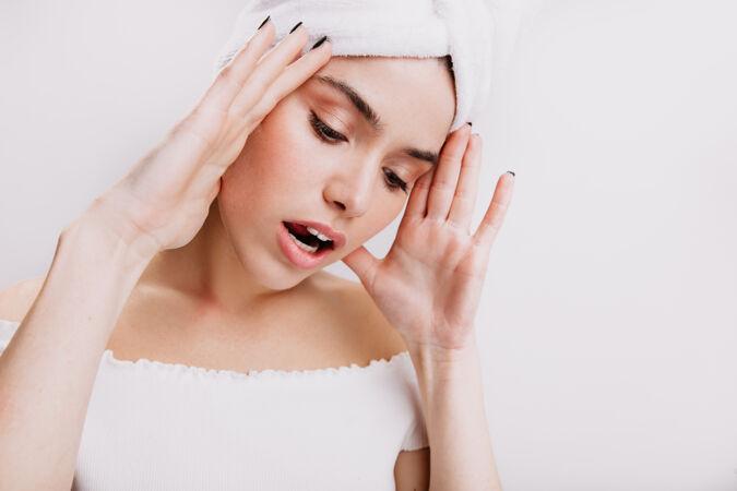 穿着白毛巾的漂亮女人头痛隔墙上皮肤健康的女孩的快照