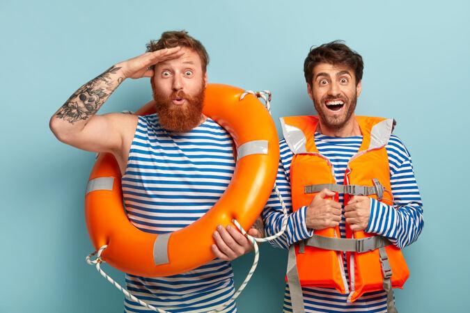 快乐的家伙们穿着救生衣和救生圈在海滩上摆姿势