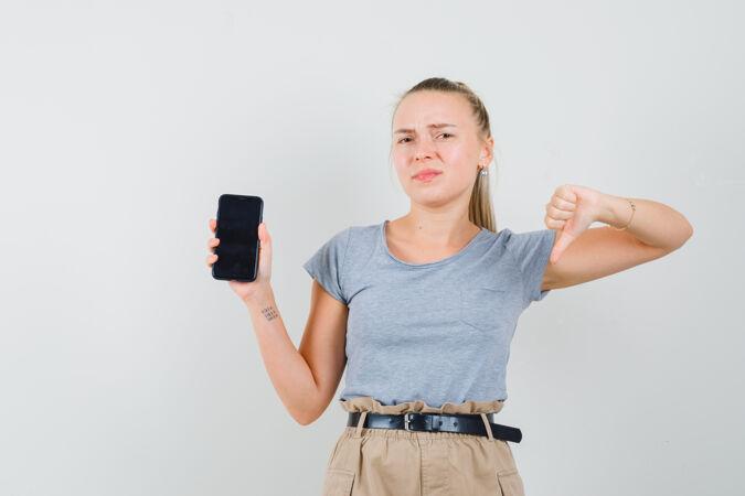 拿着手机的年轻女士 穿着t恤和裤子 拇指朝下 看起来很不满意