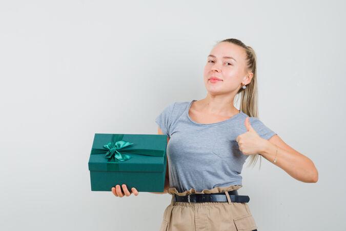 年轻的女士拿着礼物盒 在t恤和裤子里竖起大拇指 看起来很高兴