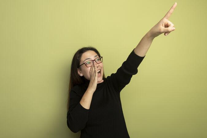 年轻漂亮的女孩穿着黑色高领毛衣 戴着眼镜 用手指着嘴巴 用食指指着什么东西