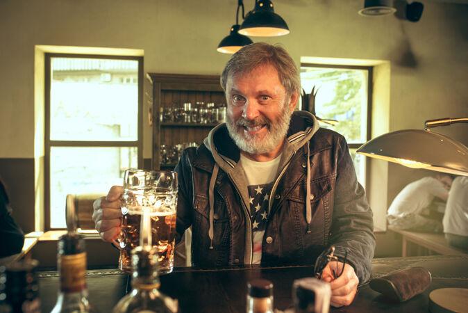 大胡子男人在酒吧喝酒 看电视上的体育节目享受我最喜欢的酒和啤酒坐在桌上喝啤酒的男人足球或体育迷人类情感的概念