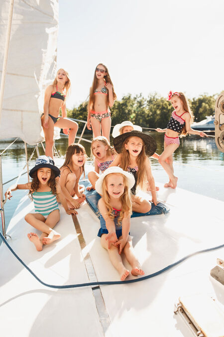 孩子们在海上游艇上青少年或儿童女孩在户外五颜六色的衣服儿童时尚 阳光明媚的夏天 河流和假日的概念