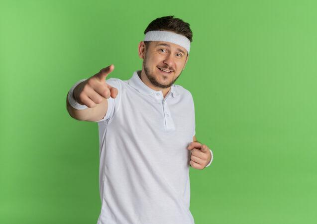 身穿白衬衫 头箍 手指对着相机 脸上带着微笑的年轻健身男子站在绿色背景下
