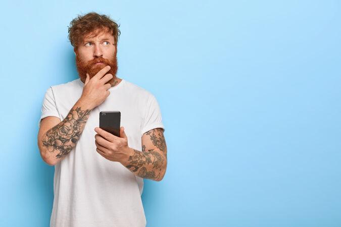 认真沉思的成年男子横拍摸着浓密的红胡子 拿着手机 上网浏览新闻 想最近的新闻 有纹身的胳膊 穿着休闲的白色t恤