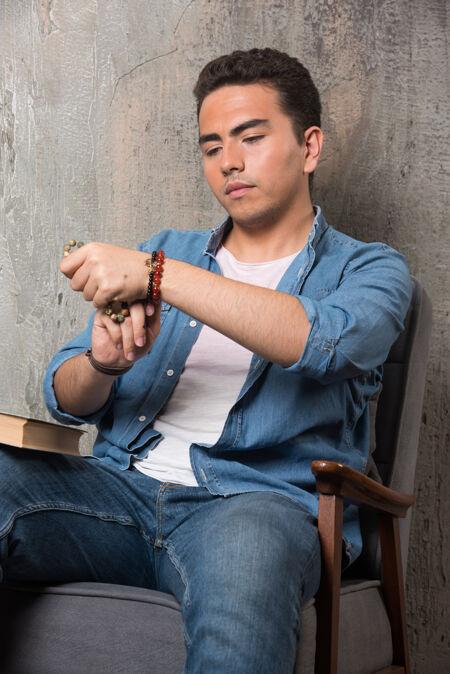 年轻人戴上手镯 坐在椅子上 把书放在大理石背景上高质量的照片