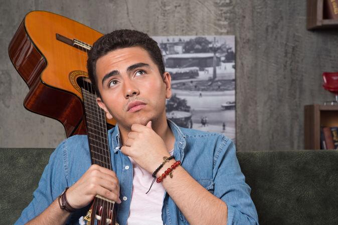 体贴的音乐家拿着一把漂亮的吉他坐在沙发上高质量的照片