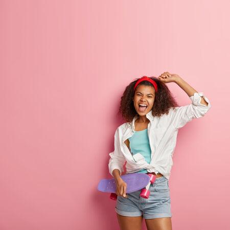 乐观的年轻美国黑人妇女举手 感到高兴 穿着白衬衫和牛仔短裤 高兴地大叫 张嘴 拿着紫色长板 模特靠着粉色的墙