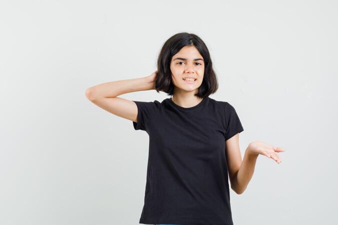 小女孩穿着黑色t恤 以质疑的方式伸出手 看上去很欢快 正前方视图