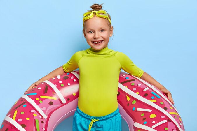 快乐姜女的半身镜头 发髻 穿着绿色t恤和蓝色短裤 带着充气泳衣 头上戴着泳镜 准备在海上游泳 和父母一起度过夏天