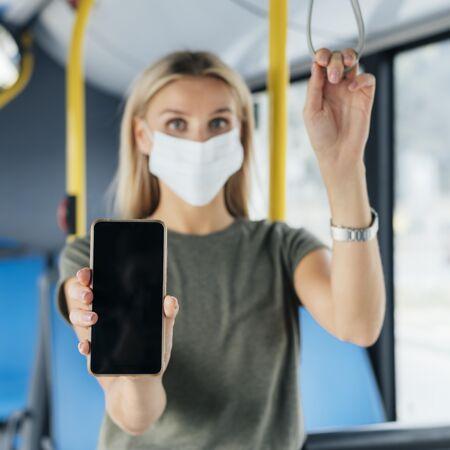 公交车上戴着医用面罩的女士举着智能手机的前视图