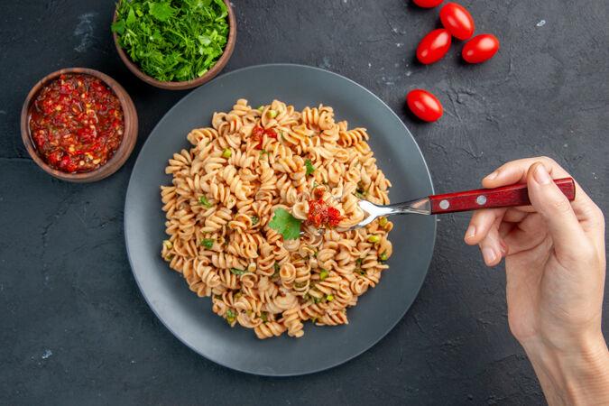 俯视图:女人手叉子上盘子里的意大利面樱桃番茄番茄酱和切碎的绿色蔬菜在黑暗的孤立表面上