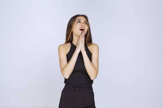 穿黑衬衫的女人双手合十祈祷