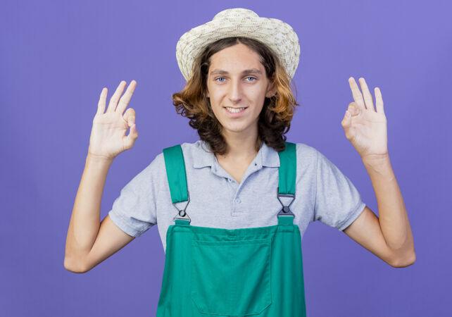 年轻的园丁穿着连体衣 戴着帽子 微笑着表示同意