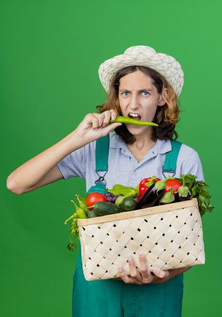 年轻的园丁穿着连体衣戴着帽子拿着装满新鲜蔬菜的箱子