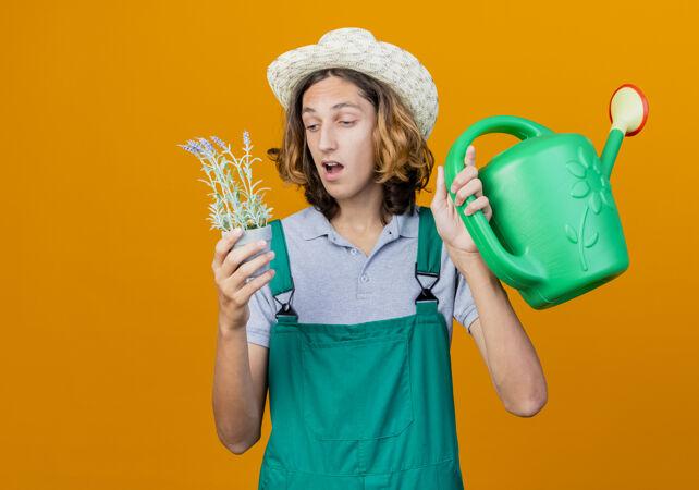 年轻的园丁 穿着连体衣 戴着帽子 手里拿着水罐和盆栽植物