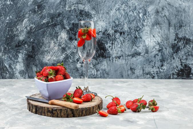 把一碗草莓放在木板上 一杯饮料放在白色和深蓝色大理石表面水平