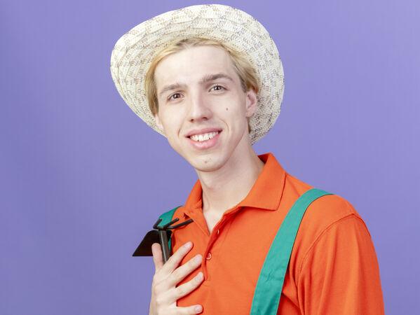 年轻的园丁穿着连体衣戴着帽子拿着床垫