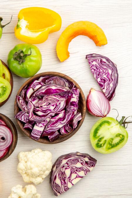 顶视图切在木碗里的红色卷心菜绿色番茄南瓜红色洋葱甜椒菜花柠檬在白色地面上